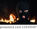 Portrait of woman in black balaclava. night fire. Concept of mass rallies,riots 53930587