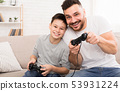 Happy boy enjoying video game with his daddy, playing with joysticks 53931224
