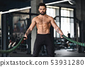 Muscular guy with naked torso exercising with battle ropes 53931280