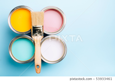 Brush with wooden handle on open cans on blue pastel background. 53933461