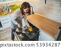 young pretty woman putting dishes in dishwasher 53934287