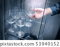 Male hand picking wine glass from cabinet 53940152