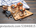 Classic tiramisu dessert with blueberries and strawberries in a glass on wooden background 53946815