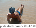 Stylish young male model man lying on beach sand wearing hipster summer hat enjoying summer travel 53954230