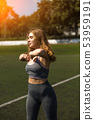 Young sportive girl with curly hairstyle on summer stadium 53959191