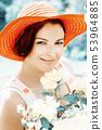 Beautiful woman in a red hat posing in garden 53964885