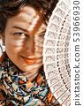 Woman peeks out from behind fan 53966930