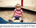 Little boy sitting in a sandbox in the yard 53977781