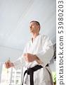 Aikido master wearing black belt having serious face 53980203