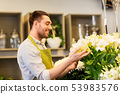 florist or seller with white lilies at flower shop 53983576