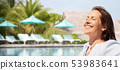 happy woman over swimming pool of touristic resort 53983641