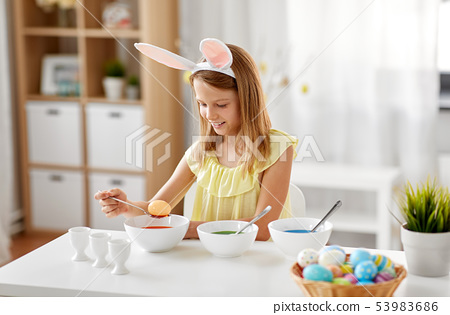 girl coloring easter eggs by liquid dye at home 53983686