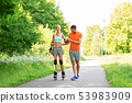 couple with roller skates riding in summer park 53983909