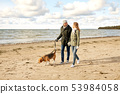 happy couple with beagle dog on autumn beach 53984058