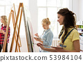 woman with easel painting at art school studio 53984104