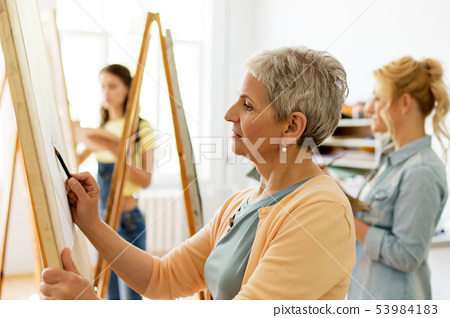 senior woman drawing on easel at art school studio 53984183