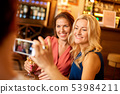 woman picturing friends by smartphone at wine bar 53984211