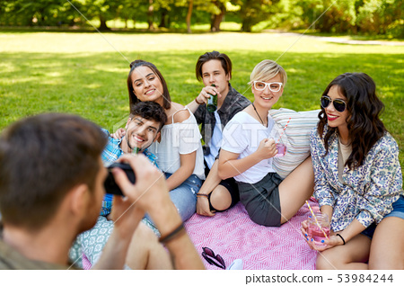 friends with drinks photographing at summer picnic 53984244
