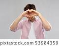 man making hand heart gesture over grey background 53984359