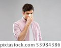 unhealthy man with paper napkin blowing nose 53984386