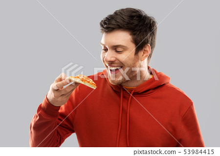 happy young man eating pizza 53984415