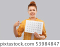 happy red haired teenage girl with calendar sheet 53984847