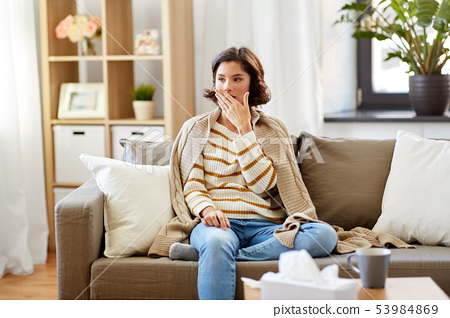 sick woman in blanket coughing at home 53984869