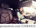 happy woman driving car with smarhphone 53984935
