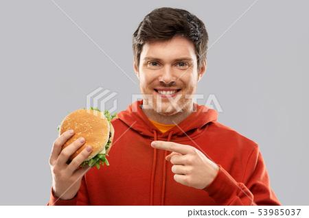happy young man showing hamburger 53985037