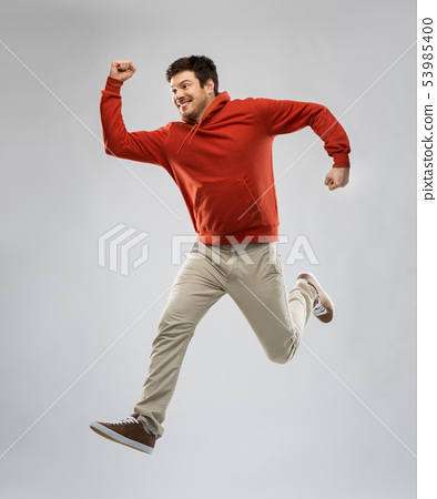 young man in hoodie jumping over grey background 53985400