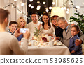 family having tea party and photographing at home 53985625