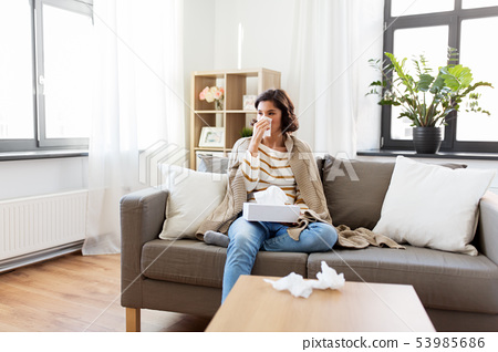 sick woman blowing nose in paper tissue at home 53985686