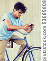 man with smartphone and fixed gear bike on street 53985808