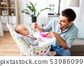 father feeding happy baby in highchair at home 53986099