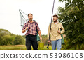 friends with fishing rods and net walking outdoors 53986108