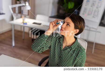 businesswoman using eye drops at night office 53986170