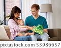 mother with baby giving birthday present to father 53986657
