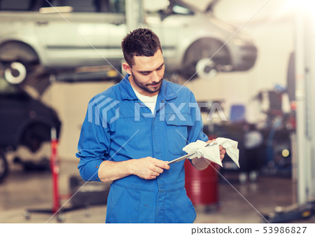 auto mechanic or smith with wrench at car workshop 53986827