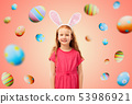 happy red haired girl wearing easter bunny ears 53986921