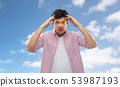 man touching his head over blue sky background 53987193