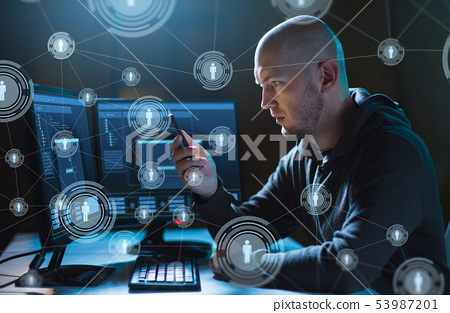 hacker with smartphone and computers in dark room 53987201
