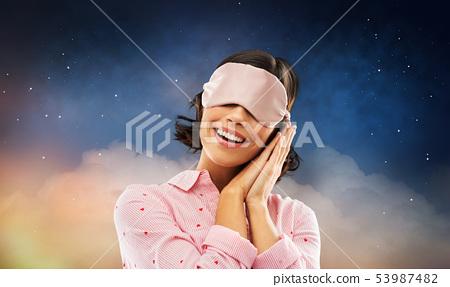 happy young woman in pajama and eye sleeping mask 53987482