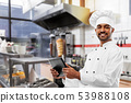 male indian chef with tablet pc at kebab shop 53988108