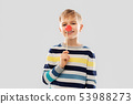 smiling boy with red clown nose party prop 53988273