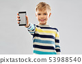 smiling boy showing blank screen of smartphone 53988540