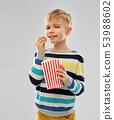 little boy eating popcorn from paper bucket 53988602