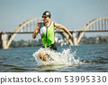 Professional triathlete swimming in river's open water 53995330