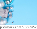Gift box and Christmas baubles on blue background. 53997457