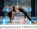 Woman doing tricks, practicing in studio with pylon.Young stripper in black  54000138
