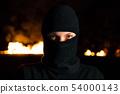 Portrait of female protesting activist in balaclava near barricades at night 54000143